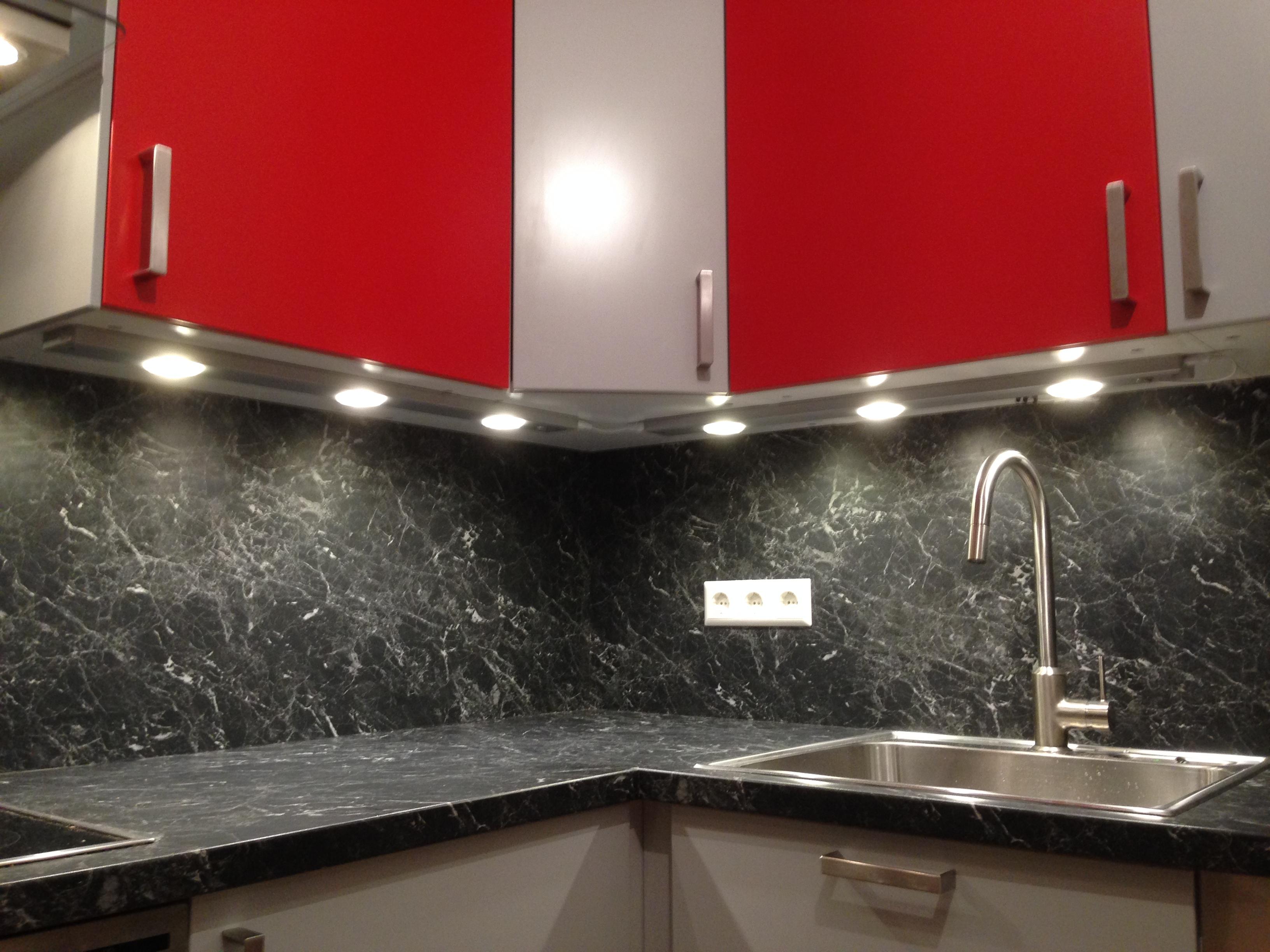 Küchenecke mit Nischenrückwand in anthrazitfarbener Steinoptik. Küchenfronten in hellgrau und weinrot gehalten.