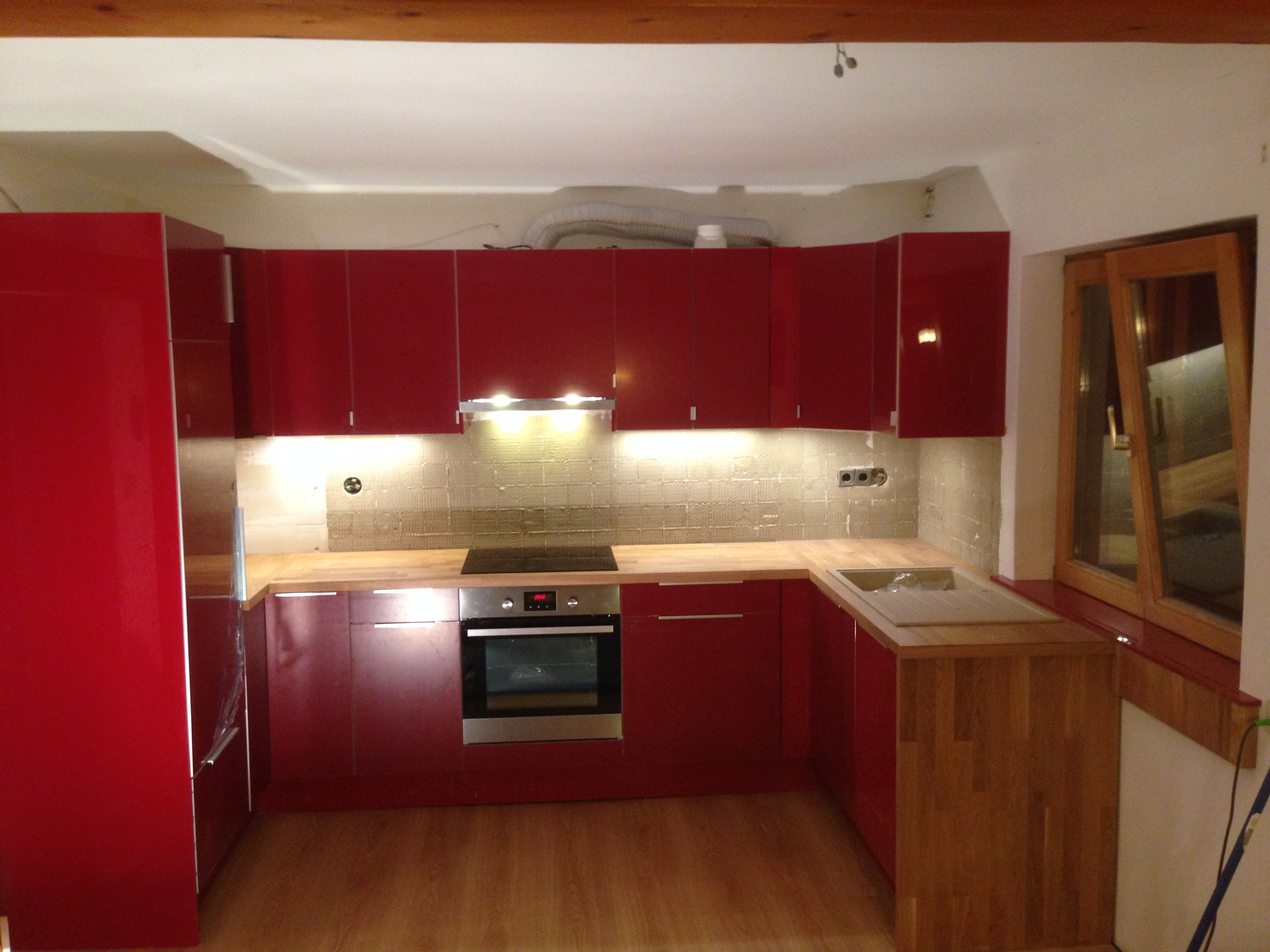 Küche in U-Form mit weinrote Fronten und Arbeitsplatte in Eiche-Vollholz. Die Fensterbank wurde in der Farbe der Küchenfronten angefertigt.