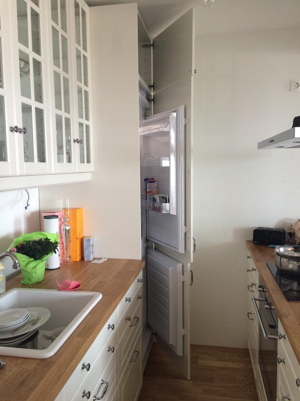 weiße Küche perspektivisch dargestellt (links und rechts). Am Ende des Bildes ist der halb geöffnete Kühlschrank ersichtlich.