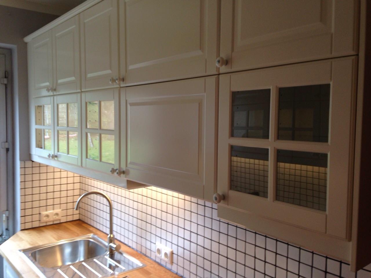 weiße Holzfronten der Oberschränke, weißer Fliesenspiegel