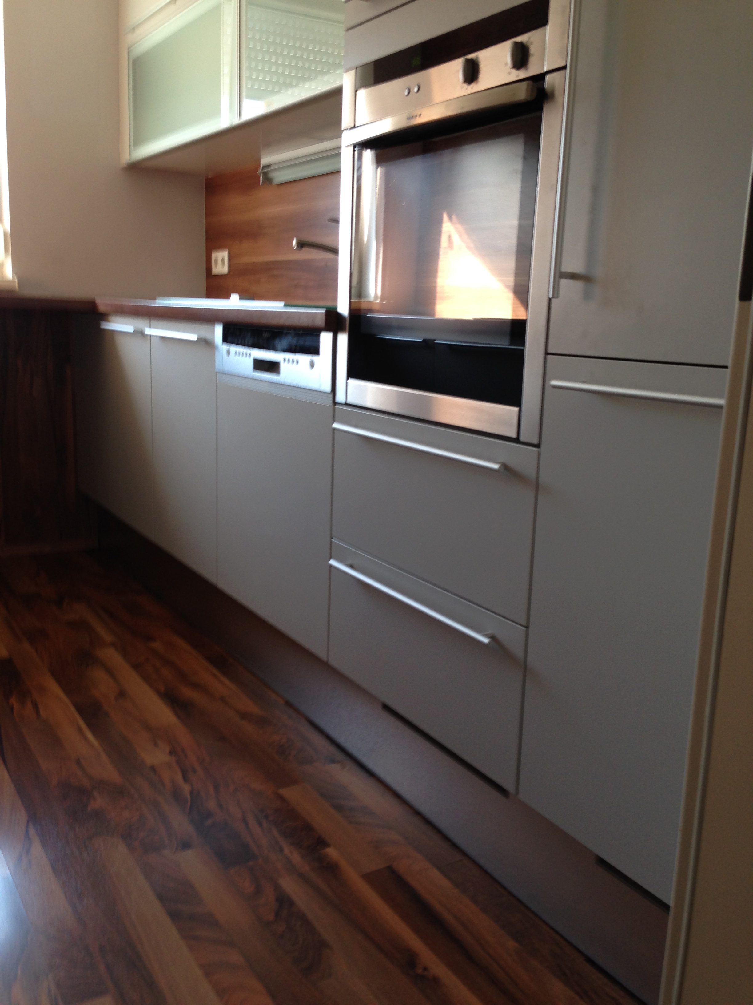 hellgraue Küchenfronten, glatte Oberfläche, Boden und Nischenrückwand in dunkler Nuss