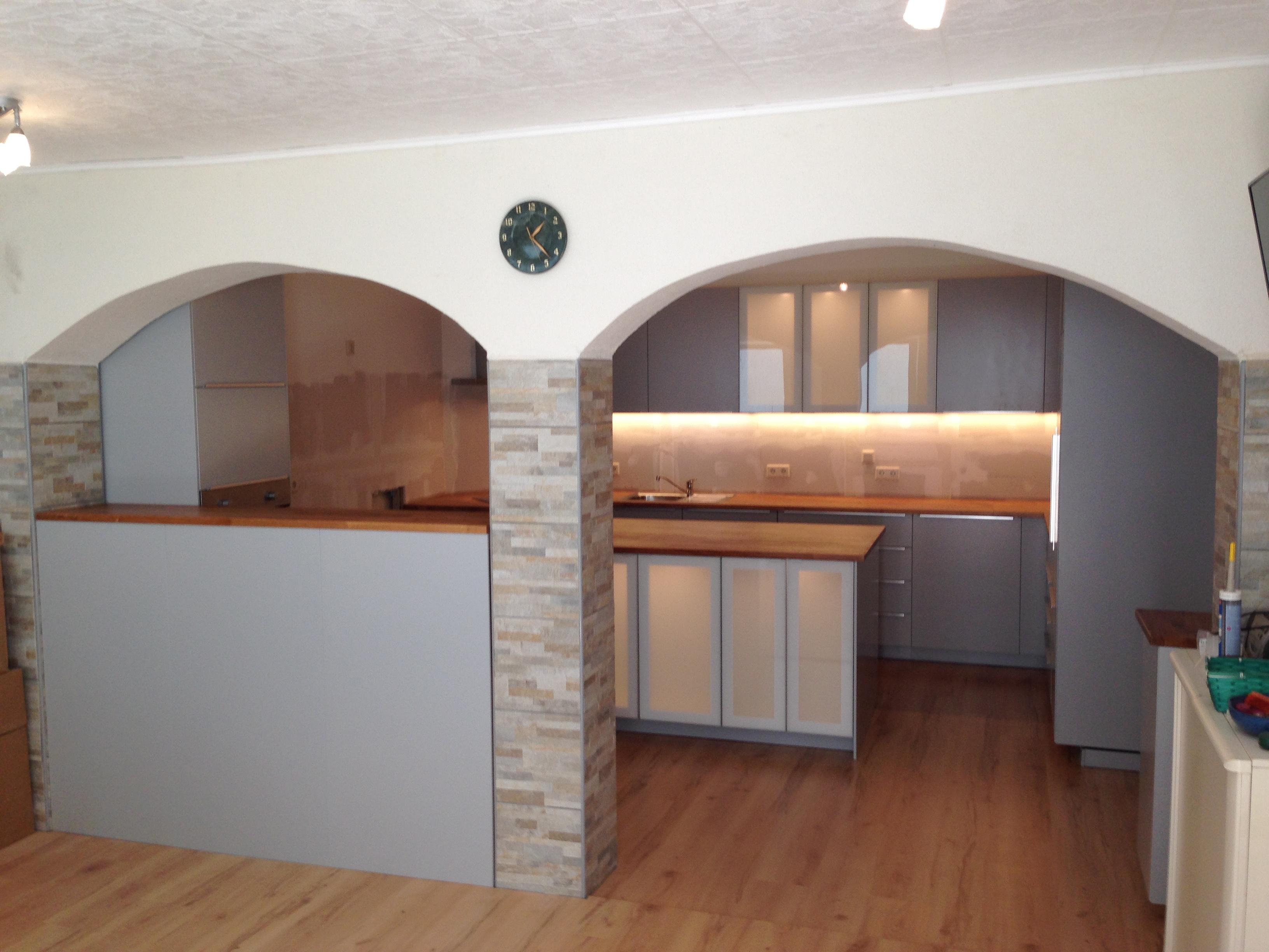 hellgraue Küchenfronten mit Kochinsel. Arbeitsplatte in Eiche-Vollholz
