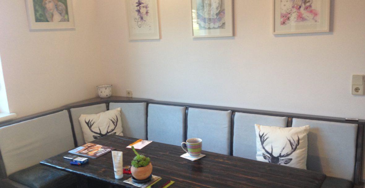 Sitzecke aus Holz. Eckbank mit Alcantarabezug in zwei unterschiedlichen Grautönen. Beim Tisch wurde die Maserung des Holzes herausgearbeitet und dunkel geölt.