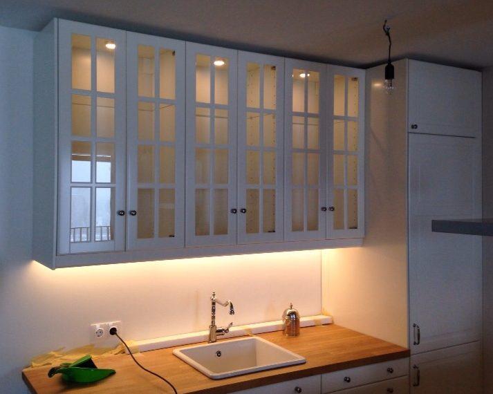 Diese weiße Küche im Landhausstil ist mit ihren beleuchteten Glasfronten an den Oberschränken ein richtiger Blickfang! Das Porzellanwaschbecken sowie die Vollholzarbeitsplatte geben ihr den nötigen Schliff.
