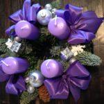 Adventkranz mit violetten Kerzen, silbernen Weihnachtskugeln und purpurnen Stoffmaschen