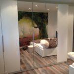 Der Kleiderschrank mit weißen Fronten und ausreichend Spiegeltüren bietet für seine Betrachter nicht nur ausreichend Stauraum, er lässt den Raum durch die gegenüberliegende Fototapete auch gleich größer erscheinen
