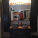 Im Hintergrund spiegeln sich auf einem gemauerten und verfliesten Podest Waschmaschine und Wäschetrockner.