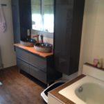 Auch die Badewanne im unteren Teil des Bildes wurde neu eingefasst und harmoniert mit den Möbeln und dem Fußboden.